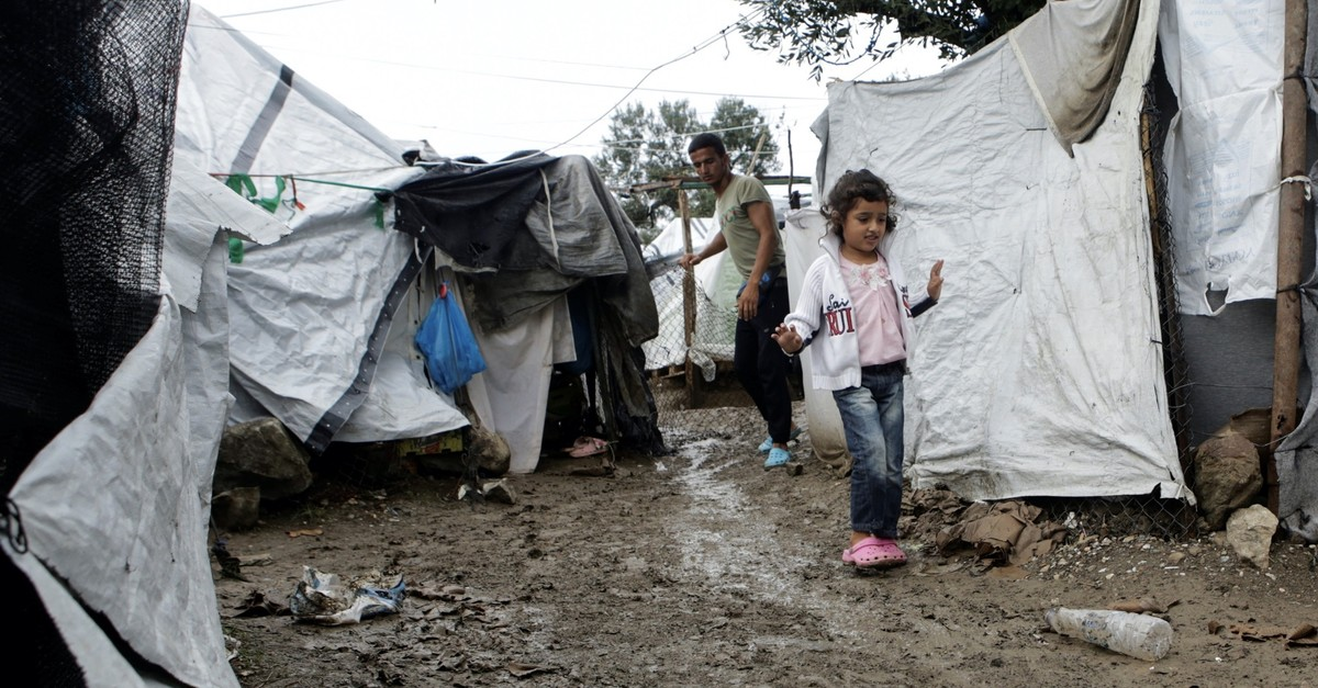 A girl makes her way at a makeshift camp for refugees and migrants next to the Moria camp, following rainfall on the island of Lesbos, Greece, Oct. 8, 2019.
