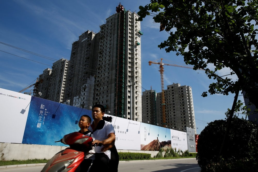 A man and a boy ride an electric scooter past the shells of apartment blocks outside a construction site in Beijing.