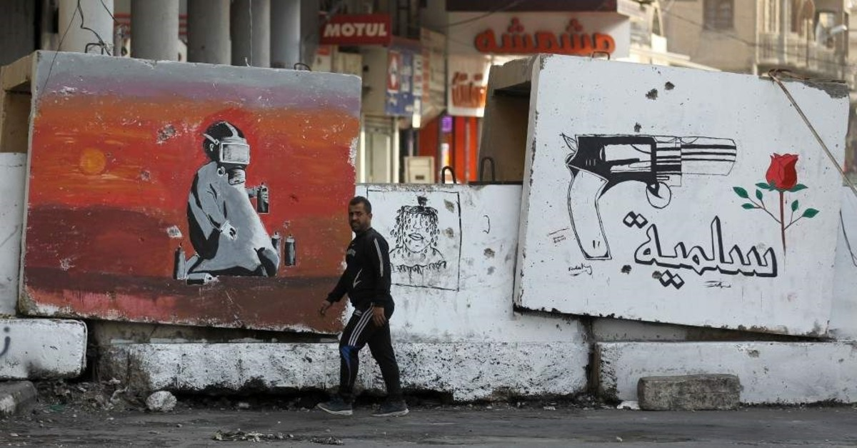 A view of a concrete barrier part of a barricade with a graffiti mural depicting a gun before a flower and text in Arabic reading ,peaceful,, Baghdad, Dec. 25, 2019. (AFP Photo)
