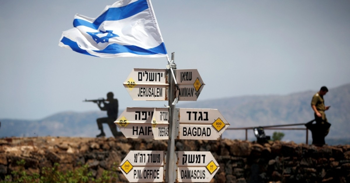 An Israeli soldier stands next to signs pointing out distances to different cities, on Mount Bental, an observation post in the Israeli-occupied Golan Heights that overlooks the Syrian side of the Quneitra crossing. (REUTERS Photo)