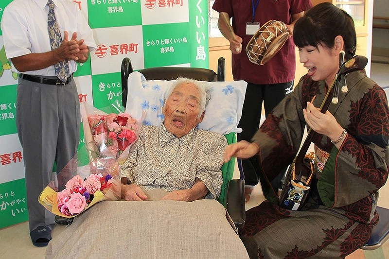 This picture received from Kikaicho Town Hall via Jiji Press, shows 117-year-old Nabi Tajima (2nd L) in Kikaicho on Kikai island of Kagoshima prefecture. (AFP Photo)