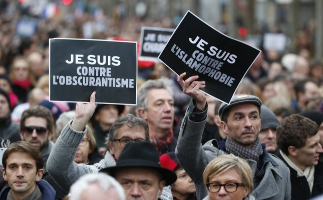 Demonstrators hold posters reading I am against obscurantism (L) and I am against Islamophobia during a march in Paris following a bloody attack by Daesh members in the French capital that killed 17, Jan. 11, 2015.