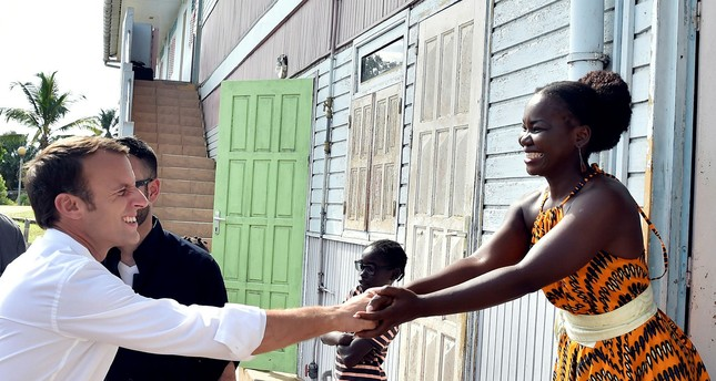 French President Emmanuel Macron shakes hands with a woman during a visit to Maripasoula, in French Guiana, Oct. 26.