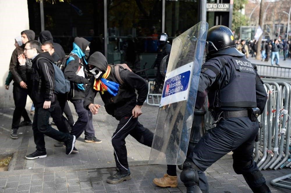 Protesters run for cover from a member of the Catalan regional police force, Barcelona, Dec. 21.