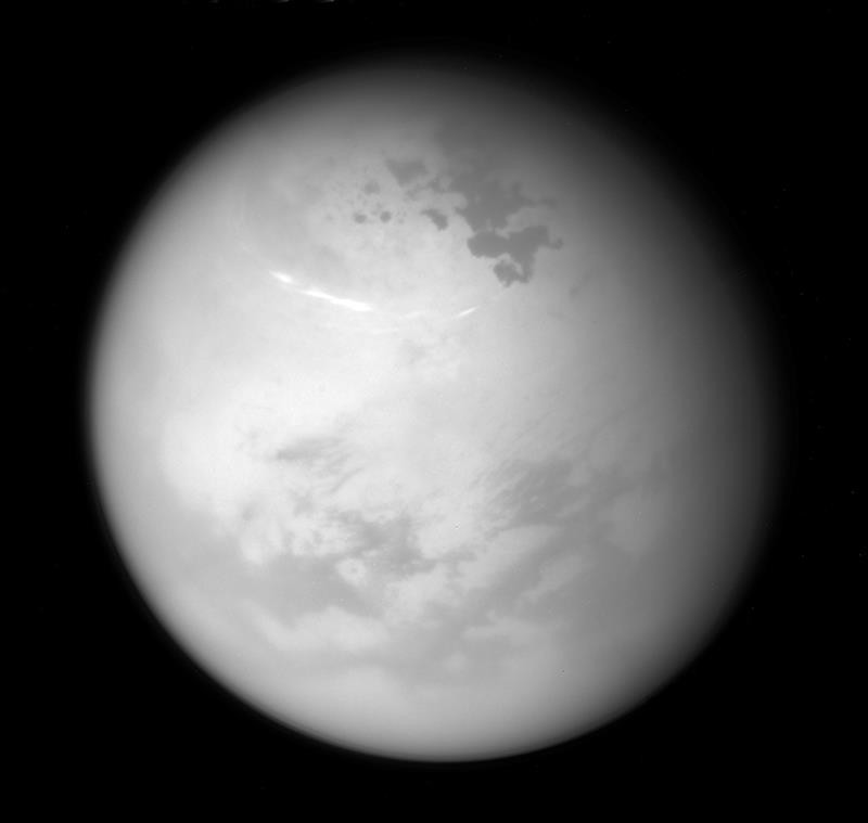 This June 9, 2017 image made available by NASA shows bright methane clouds drifting in the summer skies of Saturn's moon Titan, along with dark hydrocarbon lakes and seas clustered around the north pole, as seen from the Cassini spacecraft.