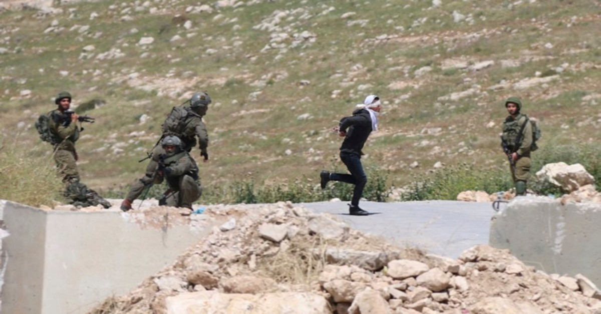 In this Thursday, Apri 18, 2019 photo, handcuffed and blindfolded Osama Hajahjeh, 16, runs away from Israeli soldiers near the village of Tekoa, West Bank. (AP Photo)
