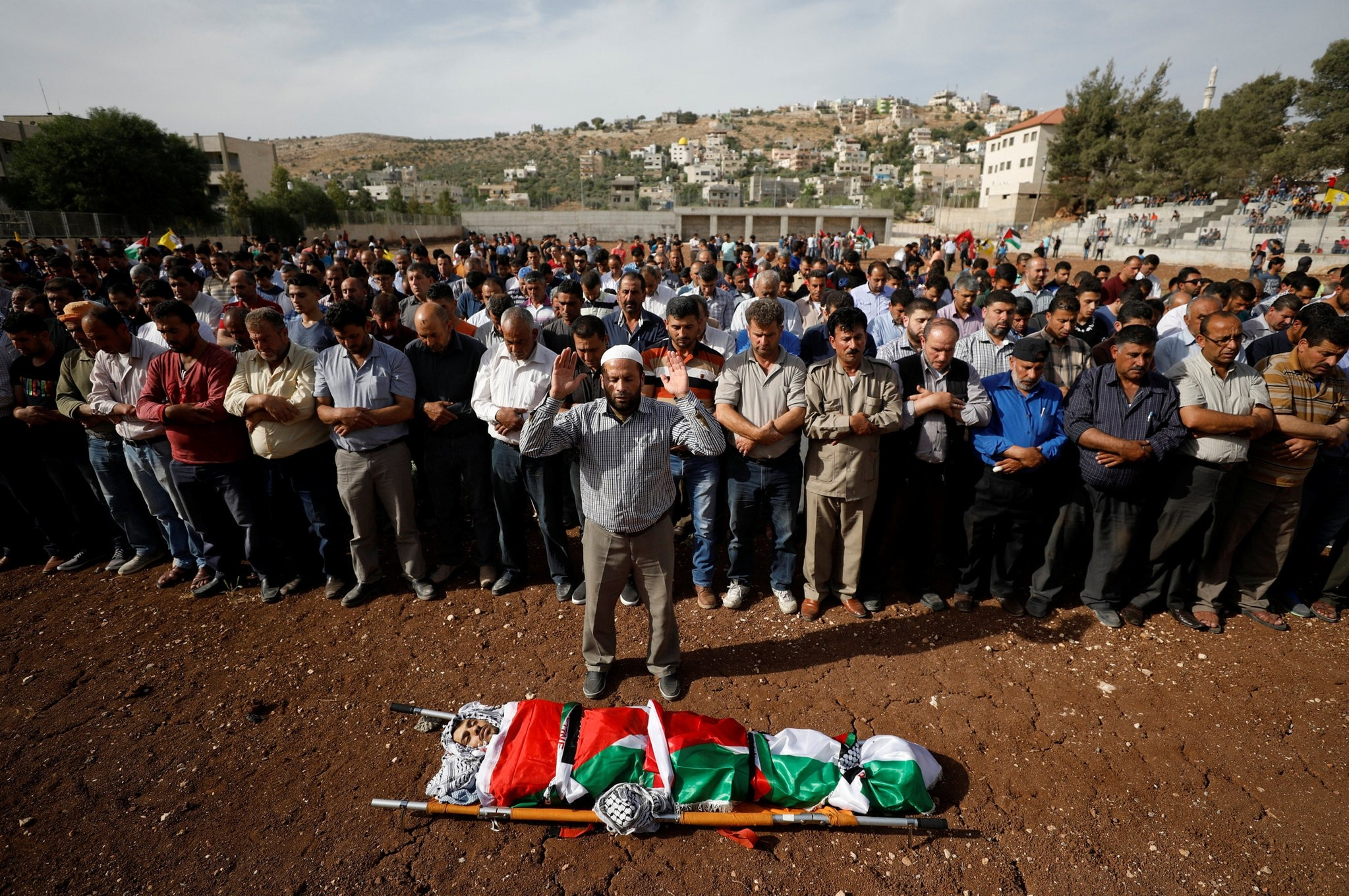 Mourners pray next to the body of Palestinian Motaz Bani Shamsa during his funeral in the West Bank village of Beita, near Nablus May 18, 2017. (REUTERS Photo)