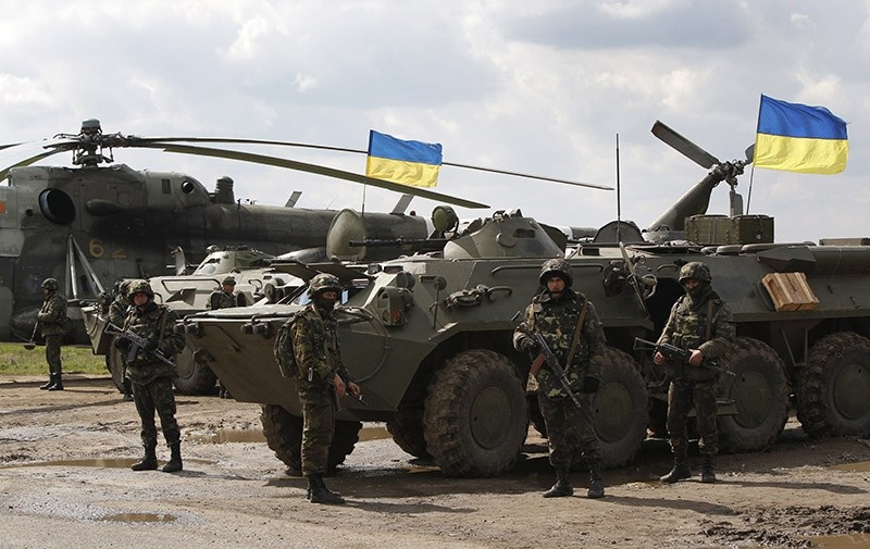 Ukrainian soldiers stand at APCs, with Ukrainian flags in the back, as Ukrainian army troops receive ammunition in a field on the outskirts of Izyum, Eastern Ukraine, Tuesday, April 15, 2014. (AP Photo)