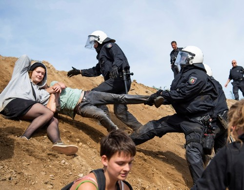 Protesters who try to enter the Hambach forest are stopped by the police in Kerpen, Germany, Sunday, Sept. 16, 2018. (AP Photo)