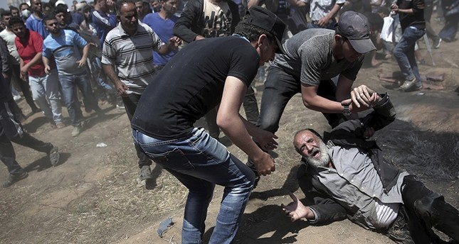An elderly Palestinian man falls on the ground after being shot by Israeli troops during a deadly protest at the Gaza Strip's border with Israel, east of Khan Younis, Gaza Strip, Monday, May 14, 2018. (AP Photo)