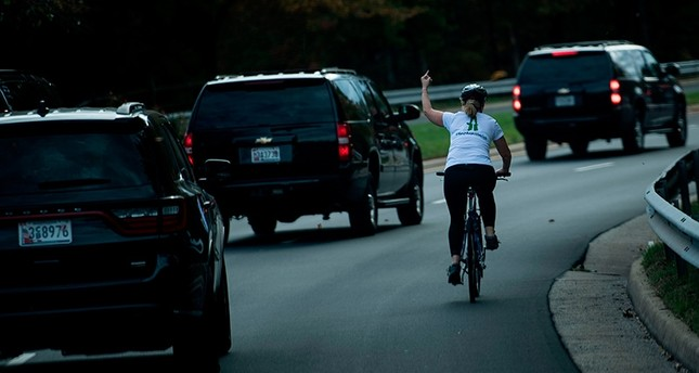 This file photo taken on October 28, 2017 shows a woman on a bike gestures with her middle finger as a motorcade with U.S. President Donald Trump departs Trump National Golf Course in Sterling, Va. (AFP Photo)