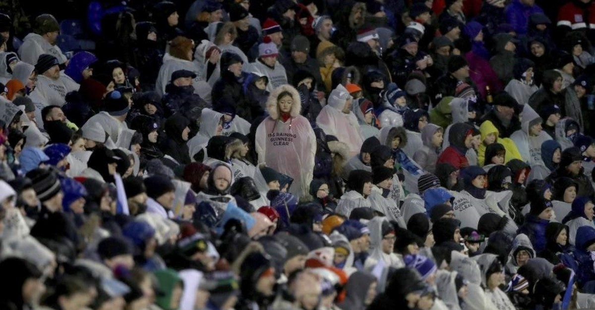 The crowd cover up from the rain as Storm Ciara hits during the Six Nations rugby union international match between Scotland and England at Murrayfield Stadium, in Edinburgh, Scotland, Feb. 8, 2020. (AP Photo)