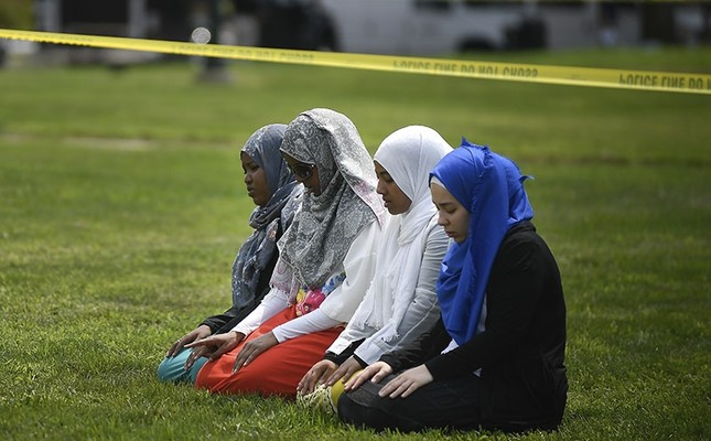 A group of women take part in afternoon prayers led by Dar Al Farooq Islamic Center Executive Director Mohamed Omar outside the police tape surrounding the center, Saturday Aug. 5, 2017 in Bloomington, Minn. (AP Photo)