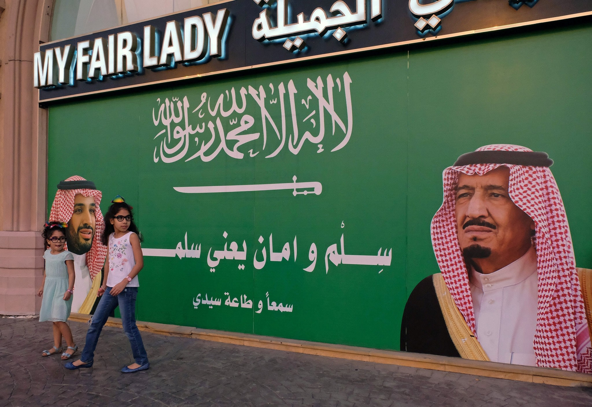 Girls stand next to a poster depicting Saudi Arabia's King Salman bin Abdulaziz Al Saud and Crown Prince Mohammed bin Salman in Jeddah, Saudi Arabia November 10, 2017. (Reuters Photo)
