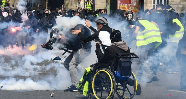 """A cameraman reacts as he is hit by a tear gas canister as a """"yellow vest"""" protester goes to help him during clashes with police in Paris, May 1, 2019."""