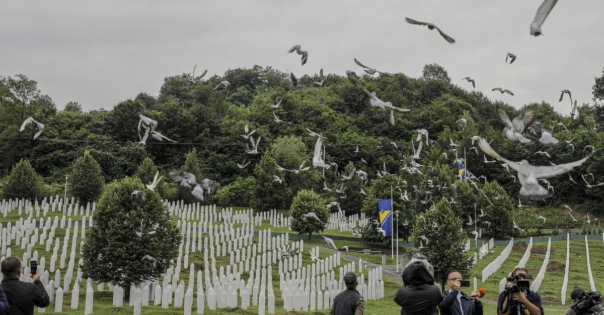 Pigeons fly over as people visit the memorial cemetery of the victims of the Srebrenica genocide, in Potocari near Srebrenica, Bosnia, July 10, 2019.