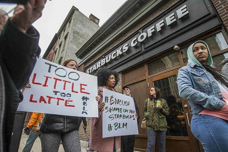Protesters gather outside of a  Starbucks in Philadelphia, Sunday, April 15, 2018, where two black men were arrested Thursday after employees called police to say the men were trespassing. (AP Photo)
