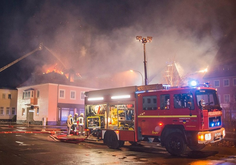 This file photo taken on February 21, 2016 shows fire fighters trying to extinguish a fire at a former hotel that was under reconstruction to become a home for asylum seekers on February 21, 2016 in Dresden, Germany. (AFP Photo)