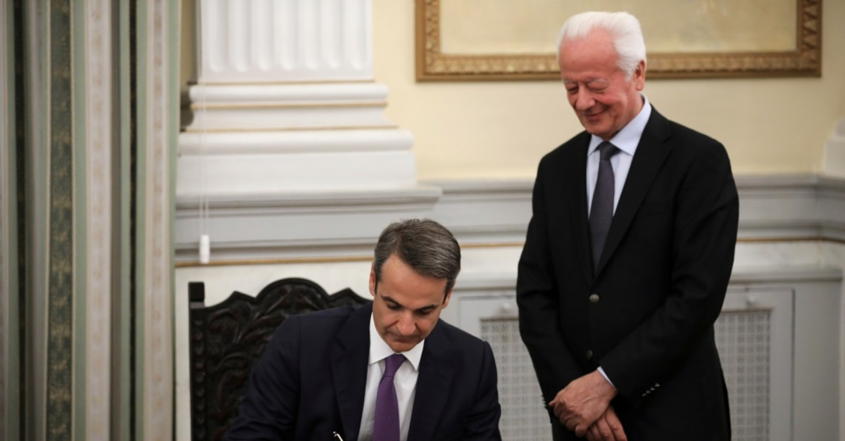 Greece's new Prime Minister Kyriakos Mitsotakis signs a document during a swearing-in ceremony at the Presidential Palace, Athens, July 8, 2019.