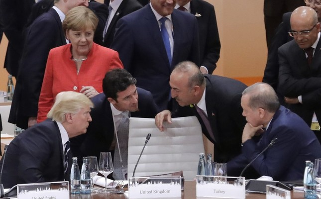 German Chancellor Angela Merkel looks on as U.S. President Donald Trump (L) talks to Foreign Minister Mevlüt Çavuşoğlu and President Recep Tayyip Erdoğan (R) prior to the first working session on the first day of G-20 summit, Hamburg, July 7, 2017.