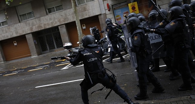 Spanish riot police shoots rubber bullet straight to people trying to reach a voting site at a school assigned to be a polling station by the Catalan government in Barcelona, Spain, Sunday, 1 Oct. 2017 (AP Photo)