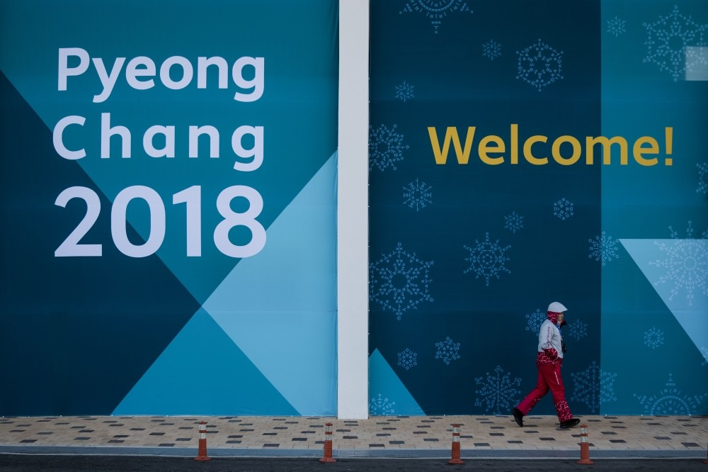 A volunteer walk past a large banner at the Gangneung Olympic Park prior to the 2018 Winter Olympics, Gangneung, South Korea, Feb. 5. AP