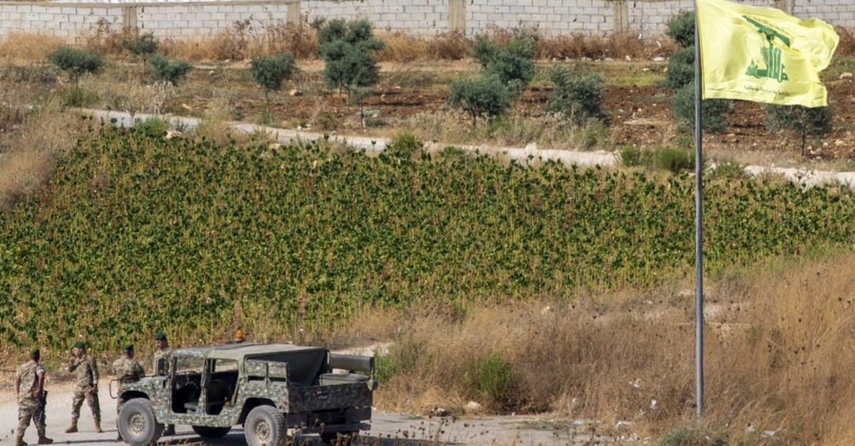 Lebanese soldiers next to a Hezbollah flag patrol in the southern Lebanese village of Aitaroun, on the Israel-Lebanon border, Israel, Tuesday, Aug. 27, 2019. (AP Photo)