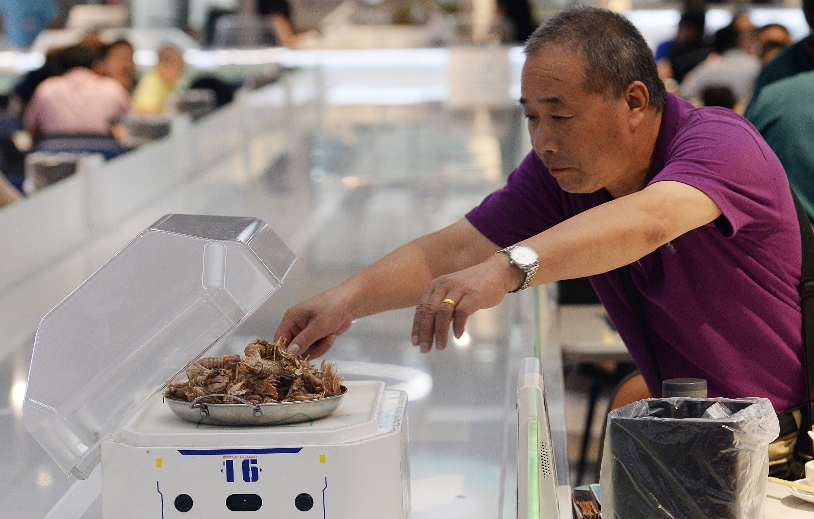 A man gets food from a robot at the ROBOT.HE restaurant in Shanghai.