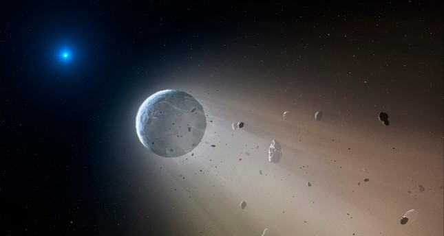 This artist's rendering provided by the Harvard-Smithsonian Center for Astrophysics shows an asteroid slowly disintegrating as it orbits a white dwarf star. On Wednesday, Oct. 21, 2015 (AP File Photo)