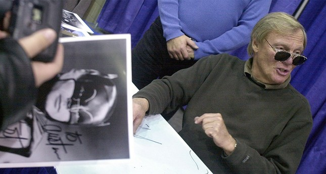 In this Feb. 23, 2002 file photo, a fan holds a signed photograph of actor Adam West, right, during the 50th Autorama in Detroit. AP Photo