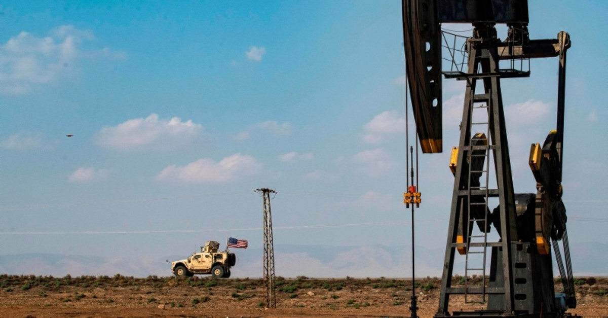 A US military vehicle, part of a convoy arriving from northern Iraq, drives past an oil pump jack in the countryside of Syria's northeastern city of Qamishli on October 26, 2019. (AFP Photo)