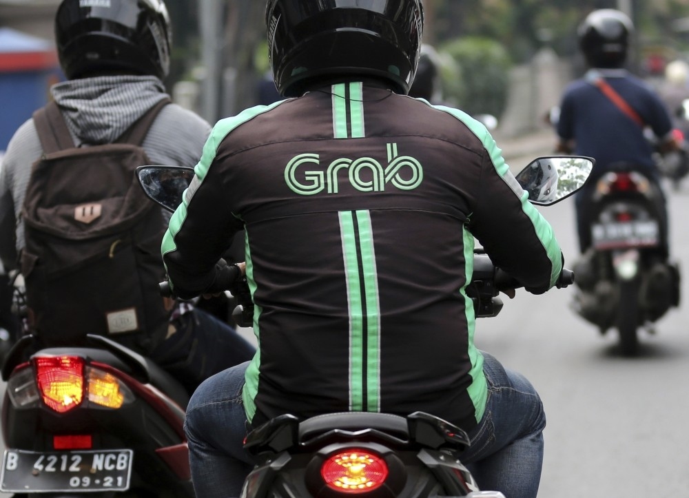 A GrabBike driver rides on a motorbike in Jakarta, Indonesia.