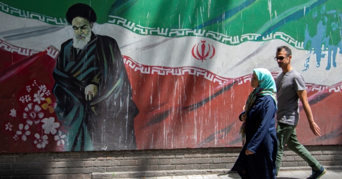 People walk in front of a mural of Iran's late leader Ayatollah Ruhollah Khomeini in Tehran, Iran July 7, 2019. Picture taken July 7, 2019. (Reuters Photo)