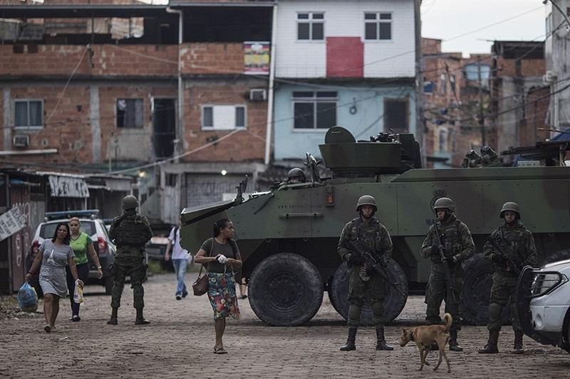 Brazilian marines stand in guard next to an armored vehicle a during surprise operation in Kelson's slum in Rio de Janeiro, Brazil, Tuesday, Feb. 20, 2018. (AP Photo)