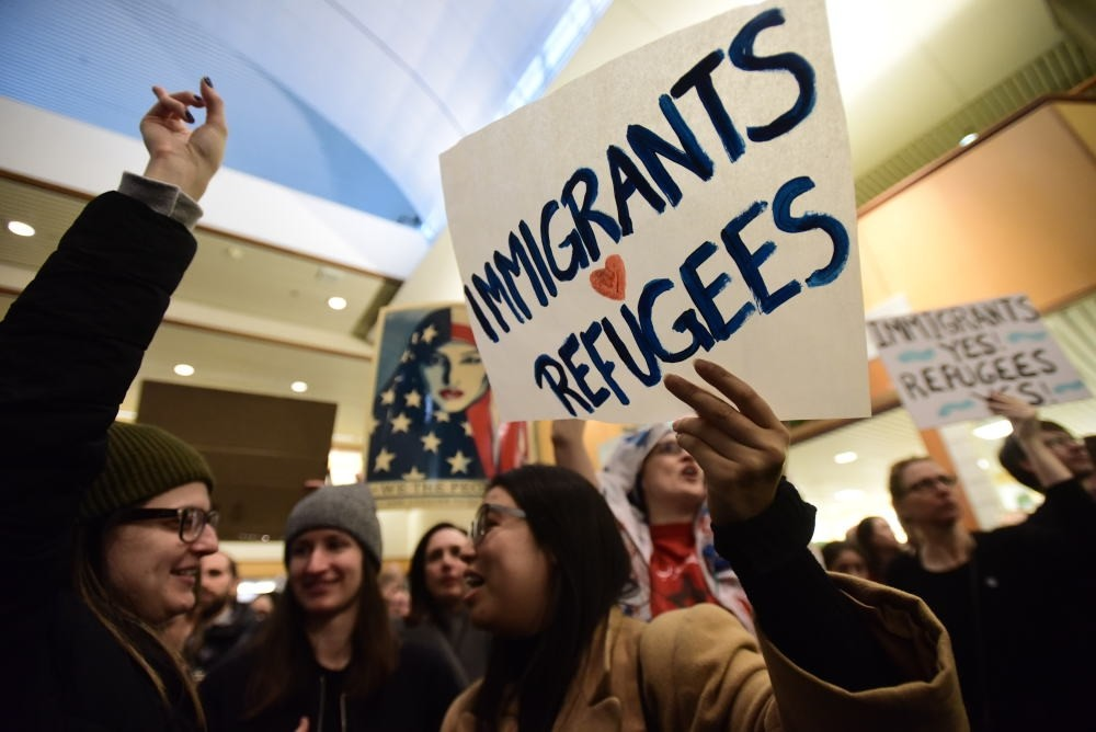 Protesters hold signs as they block a road during a demonstration against the immigration ban at Los Angeles International Airport.