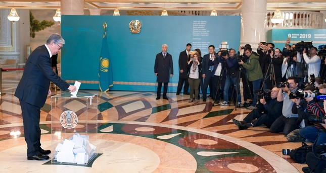 Kazakhstan's acting President Kassym-Jomart Tokayev, left, casts his ballot at a polling station during the presidential elections in Nur-Sultan, the capital city of Kazakhstan, Sunday, June 9, 2019. (AP Photo)