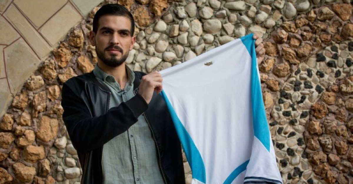 Palestinian Karam Qawasmi, who was shot in the back by Israeli forces in an incident caught on video last year, holds up the shirt he was wearing when he was shot, in the garden of his house, in the West Bank city of Hebron, Sunday, Nov. 10, 2019. (AP Photo)