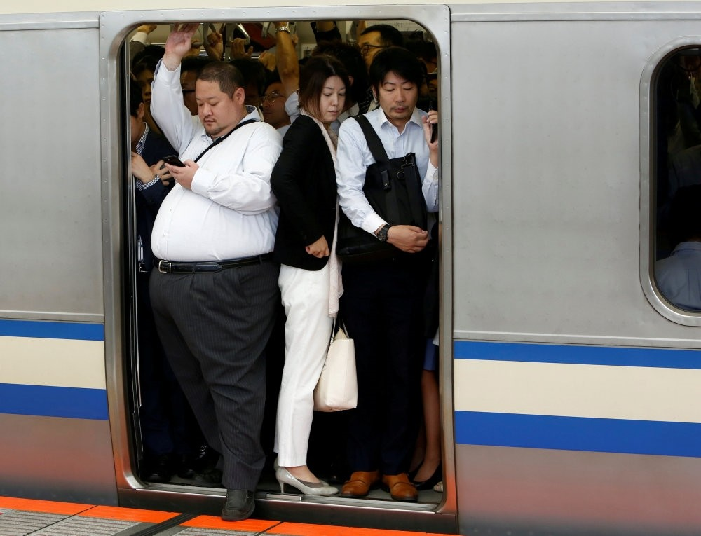 Passengers ride an overcrowded train at a station in Kawasaki, Japan.