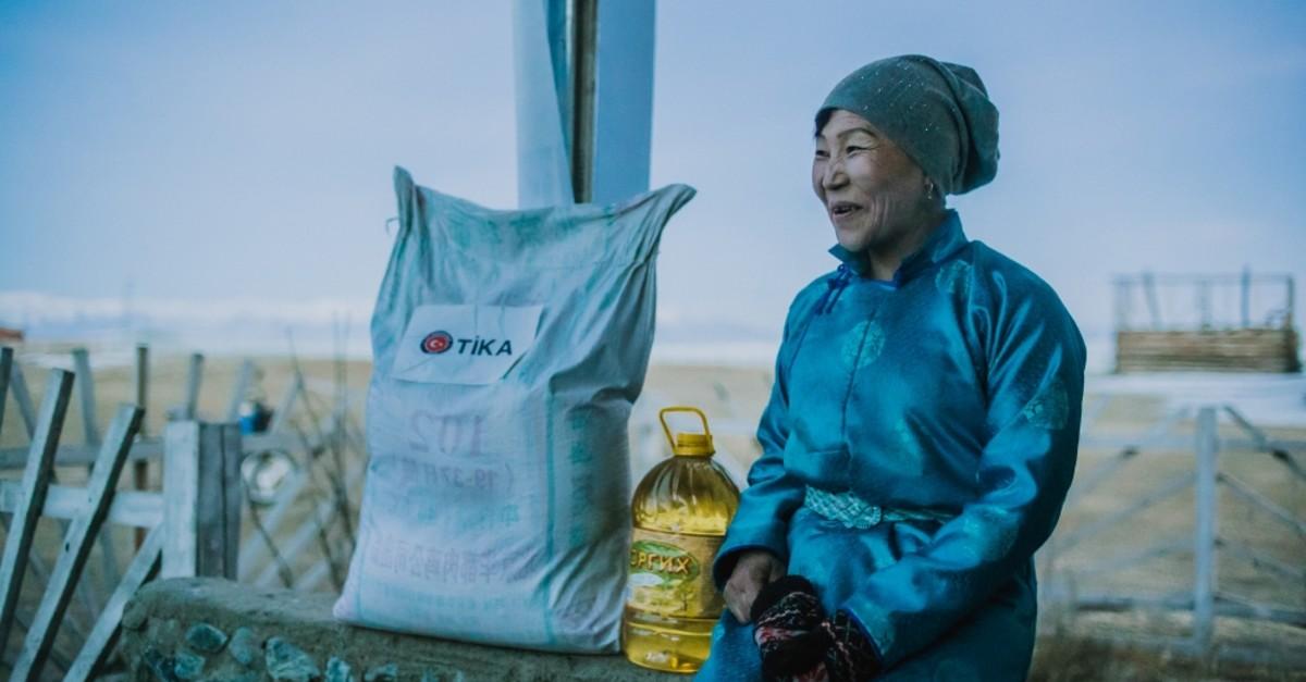 A Dukha woman sits next to food distributed by Tu0130KA in Tsagaannuur, Feb. 27, 2019.