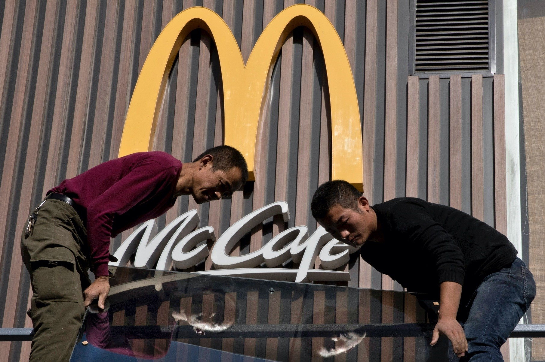 Chinese workers install glass panels near the logo for U.S. fast food brand McDonaldu2019s in Beijing.