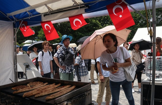 A Japanese woman  looks at Turkish pide on display at the Turkish Food Festival  in Tokyo, Japan.