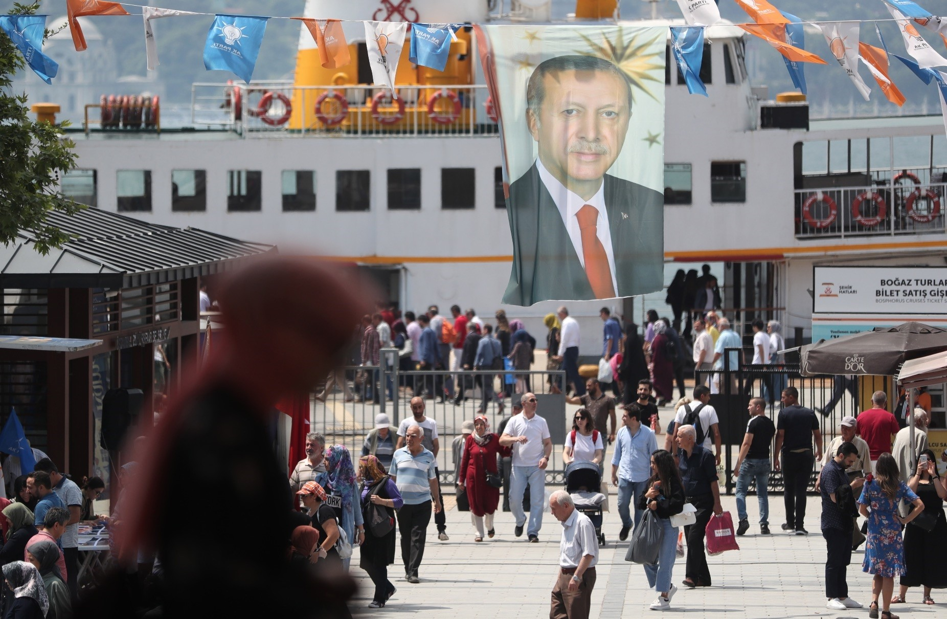 People walk under a huge picture of Turkish President Recep Tayyip Erdou011fan in Istanbul weeks before the elections on June 24. The Turkish growing economy is expected to continue to expand in the coming years under Erdou011fanu2019s stewardship.