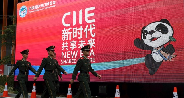 Paramilitary policemen march past a billboard for the China International Import Expo on the eve of its opening in Shanghai, Nov. 4.