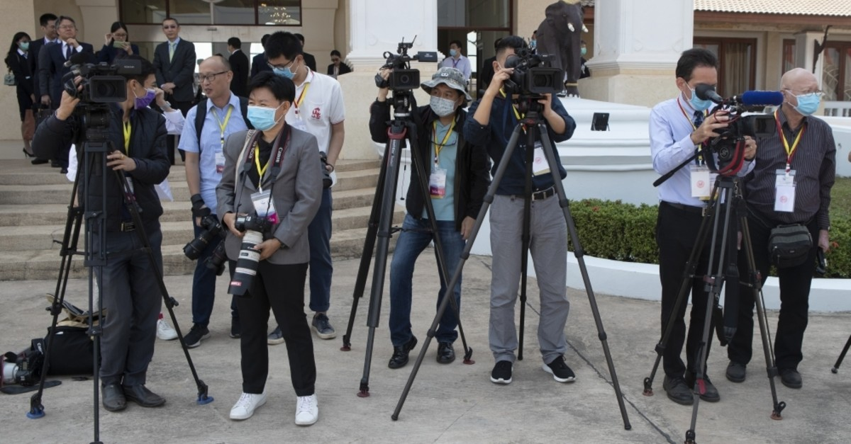 Members of media wear face masks for protection while waiting for Chinese Foreign Minister Wang Yi's arrival at Wattay Airport in Vientiane, Laos, Feb. 19, 2020. (AP Photo)