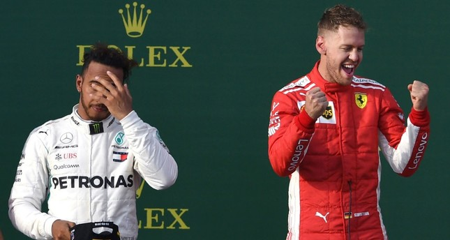 Ferrari's Vettel celebrates his win on the podium with Mercedes' Hamilton in the background on March 25.
