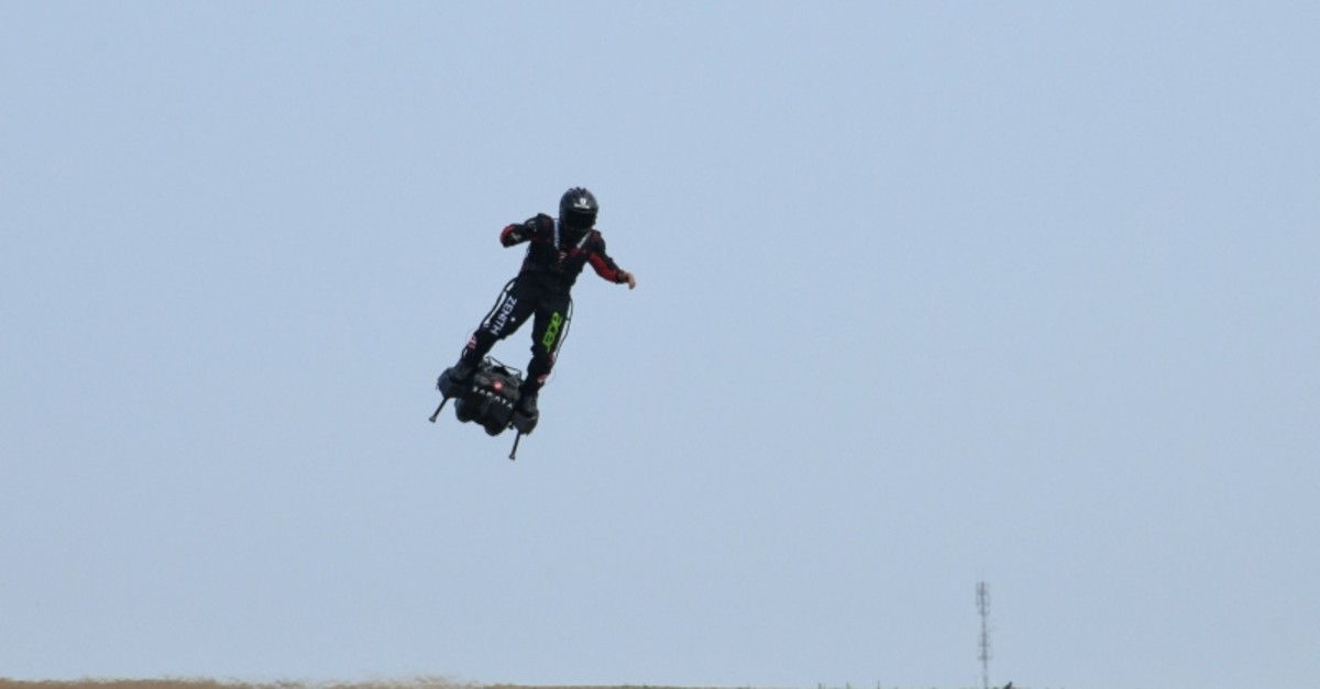 Zapata CEO Franky Zapata flies over fields on his jet-powered hoverboard or ,Flyboard, during a test flight in Saint-Inglevert, northern France, on July 24, 2019 (AFP Photo)