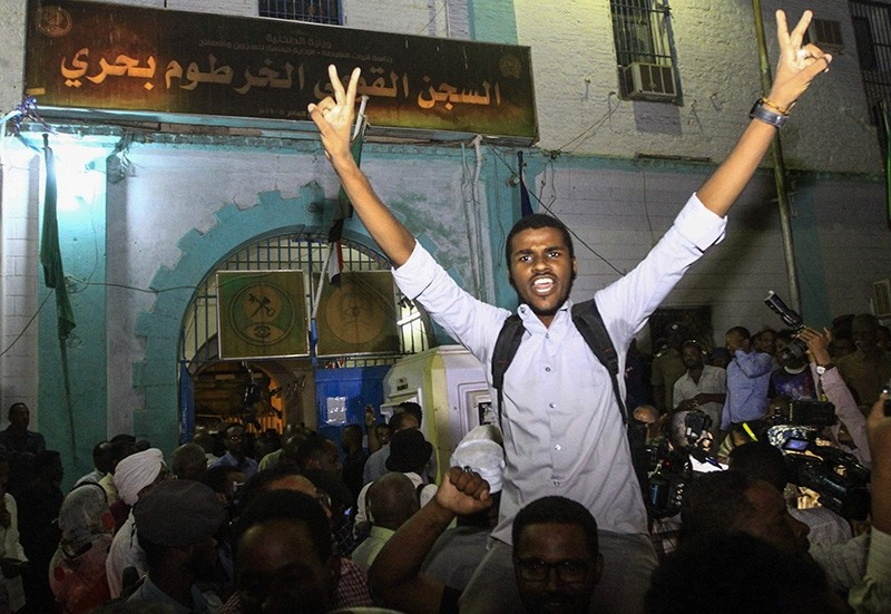 Family members shout slogans as they wait outside the Kobar prison in north Khartoum to welcome their loved ones after Sudan released dozens of opposition activists who were arrested last month. (AFP Photo)