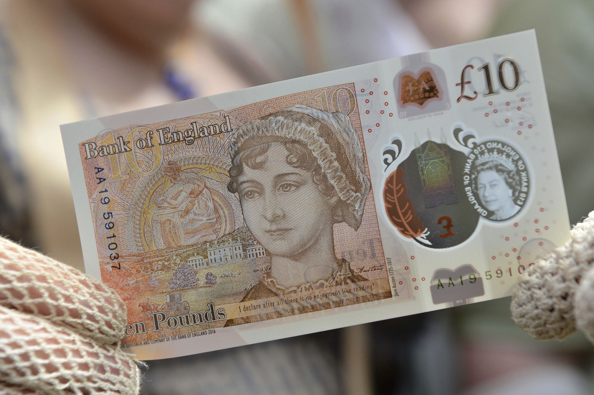 People in period costume pose with on the Bank of England's new ten pound notes, featuring author Jane Austen, during its launch at Winchester Cathedral in Winchester, on July 18, 2017. (AP Photo)