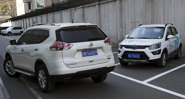 A SUV vehicle (L) drives past an electric-powered SUV parked outside a shopping mall in Beijing. This month's Shanghai auto show, industry's biggest marketing event of year, will showcase efforts to create electric models Chinese drivers want to buy.