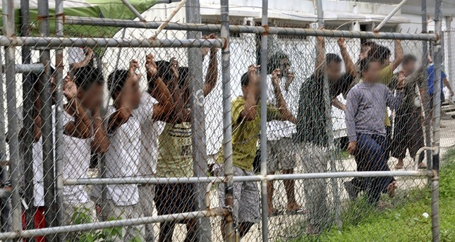 Asylum seekers staring at media from behind a fence at the Oscar compound in the Manus Island detention center, Papua New Guinea, March 21, 2014. (EPA Photo)